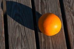Fruit orange sur un banc en bois à la lumière du soleil de pente Le fruit Ca image stock