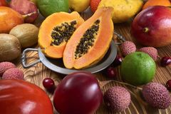 Fruit papaya on a metal plate, around a lot of fruits of a different species. Papaya on plates among many other exotic fruits. On wooden boards Stock Image