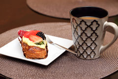 Fruit pastry. A mug of coffee and fruit pastry on a white plate with a little fork Royalty Free Stock Photography