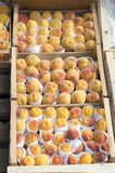 The fruit of peaches is wrapped for sale in wooden boxes on the outdoor window. royalty free stock photography