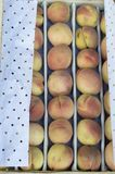The fruit of peaches is wrapped for sale in wooden boxes on the outdoor window. stock photos