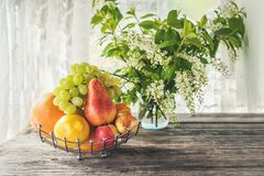Fruit pear, grapefruit, lemon, peach are in the basket on the background of a bouquet of small white flowers of bird Royalty Free Stock Photography