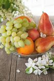 Fruit, pear, grapefruit, lemon, peach, strawberry in a basket on the background of a bouquet of small white flowers on a Sunny day Royalty Free Stock Images