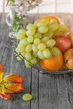 Fruit, pear, grapefruit, lemon, peach, strawberry in a basket on the background of a bouquet of small white flowers on a Sunny day Stock Images