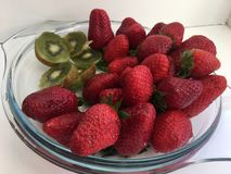 A plate with juicy ripe berries strawberries and kiwi. Fruit photography. in a transparent plate lies a fresh, large, red strawberry and sliced kiwi slices Royalty Free Stock Photography