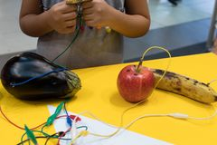 Fruit piano with kids. STEM education activity allow kids to play music with fruit and vegetables. Microcontroller converts keys. In sound with some fruits royalty free stock images