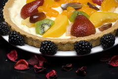 Fruit pie. A fruit pie on a white plate on a black background royalty free stock photography