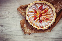 Fruit pie. With peaches and red currants on a wooden background. traditional pastries. view from the top royalty free stock photo