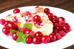 Fruit pie on plate with cherries and raspberries. Horizontal photo of fruit pie on white plate among heap of red juicy cherries and sweet raspberries. Single royalty free stock images