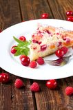 Fruit pie on white plate with berries. Vertical photo of single portion of fruit pie cake placed on white plate with several berries, melissa branch and fork stock photos