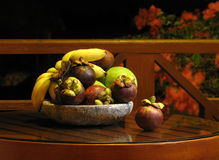 The fruit piece from Bali:. Few purple-brown mangosteen manggis, fresh salak and ripe bananas. The decorative plate with exotic fruit on the glass-wooden table Royalty Free Stock Photography