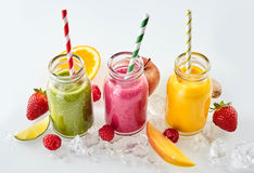 Fruit pieces and smoothies in a row royalty free stock photography
