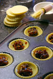Fruit pies being prepared in a kitchen enviroment. With pastry tops and brush in the out-of-focus background.  These are mince pies, traditional fare at Royalty Free Stock Photo
