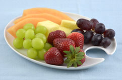 Fruit plate. Fresh fruit on a white plate with blue background Stock Photos