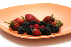 Fruit plate. Orange plate with blackberrys, raspberrys and strawberrys Stock Images