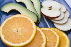 Fruit plate. A blue plate with slices on orange apple and avocado Stock Photography