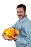 Fruit on a Plate. Young man holding a silver plate with citrus fruit Stock Photography