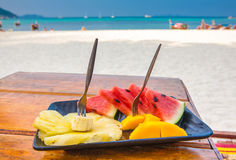 Fruit plate on the beach. The fresh tropical fruit on the beach. Plate with fruits on the tropical sea background. The fresh tropical fruit on the plate. Plate Royalty Free Stock Photography