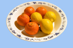 Fruit plate blue. Lemons and mandarins in a dish against a blue background Royalty Free Stock Photos