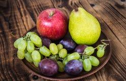 Fruit plate grapes apple plum pear Stock Photos