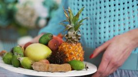 Fruit on a plate in the hands. Of a girl stock footage