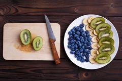 Fruit plate making. Blueberries, banana and kiwi slices on a pla royalty free stock photos