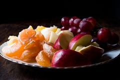 Fruit Plate with Purple Grape, Orange, Mandarin and Apple. Dark Moody Stock Image