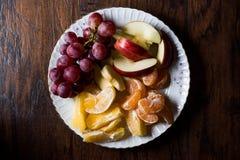 Fruit Plate with Purple Grape, Orange, Mandarin and Apple. Dark Moody Stock Photo