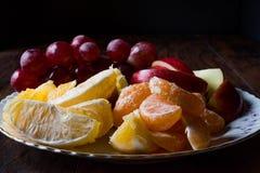 Fruit Plate with Purple Grape, Orange, Mandarin and Apple. Dark Moody Royalty Free Stock Photography
