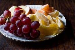 Fruit Plate with Purple Grape, Orange, Mandarin and Apple. Dark Moody Royalty Free Stock Image