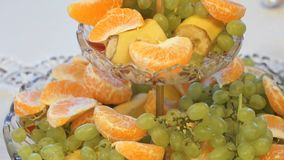 Fruit on plate with banana, tangerine, grape. Fruit on the plate on the table with pieces of banana, tangerine and grape slices on table at the celebration stock video footage