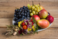 Fruit plate with wild flower decorations on the wood table Royalty Free Stock Images