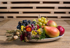 Fruit plate with wild flower decorations on the wood table Royalty Free Stock Photos