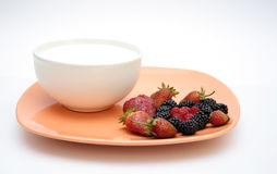 Fruit plate and yogurt. Orange plate with blackberrys, raspberrys and strawberrys, and a bowl of yogurt Stock Images