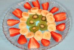 Fruit platter. Strawberries, bananas, and kiwi fruit on a glass platter Royalty Free Stock Photos