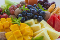 Fruit platter close-up. Colorful summer fruit platter with mango, pineapple, watermelon, grapes, cherries, apricots, strawberries, cantaloupe, walnuts and mint Stock Images