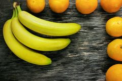 Fruit platter of fresh mandarins and bananas on gray wooden table Royalty Free Stock Image