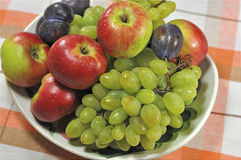Fruit on a platter. Grapes, plums and apples beautifully stacked on a platter Royalty Free Stock Photo