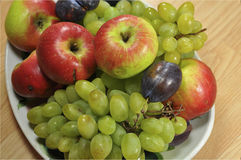 Fruit on a platter. Grapes, plums and apples beautifully stacked on a platter Stock Images