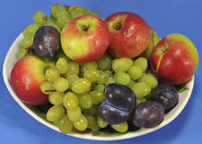 Fruit on a platter. Grapes, plums, apples beautifully stacked on a plate on a blue background Stock Photo