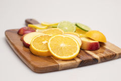 Fruit Platter. A group of various colourful fruits stacked on a wooden board Stock Image