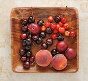 Fruit platter - peaches, plums, cherries on a wooden platter. Fruit platter - peaches, plums, cherries on a wooden platter - top view royalty free stock photography