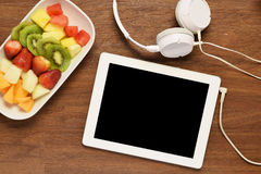 Fruit platter and tablet on a wooden tablet. Top view of fruit platter and tablet with copyspace on wooden table. Healthy and fitness concept stock photography
