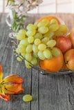 Fruit, poire, pamplemousse, citron, pêche, fraise dans un panier sur le fond d'un bouquet de petites fleurs blanches un jour enso Images stock