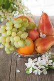 Fruit, poire, pamplemousse, citron, pêche, fraise dans un panier sur le fond d'un bouquet de petites fleurs blanches un jour enso Images libres de droits