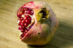 Fruit pomegranate on a textured wooden surface Royalty Free Stock Photography