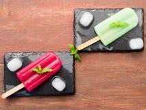 Fruit popsciles on black slate plates Stock Photography