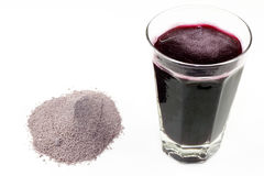 Fruit Powder and Juice. Violet purple dried and ground extract mix of berries and similar with a glass of the beverage made with water Royalty Free Stock Photography