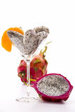 Fruit pulp of the pitaya in a glass. Pieces of pitaya pulp assorted in a cocktail glass and decorated with a mandarine slice. Next to it is a halved, and behind Royalty Free Stock Image