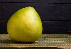 Fruit of a pummelo on an wooden table. Fruit of a pummelo on an old wooden table Royalty Free Stock Photography